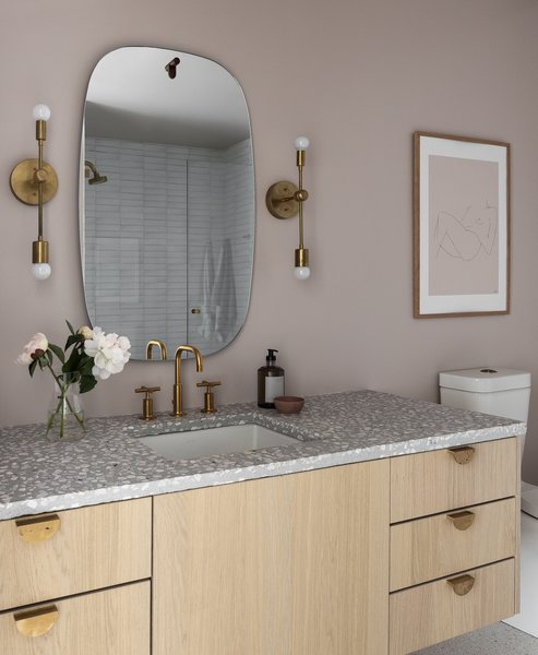 A guest bathroom is awash in blush for a lighter departure from the other, featuring a Concrete Collaborative countertop and hardware and sconces from Park Studio LA.