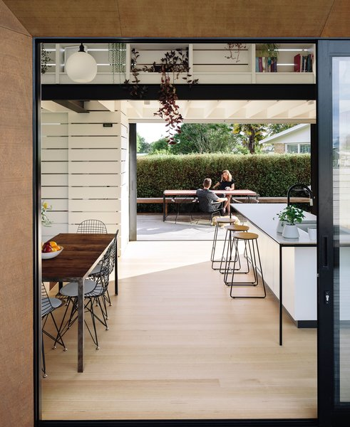 """Light and volume is key to the design of a small home, and we prioritized living spaces with great views,"" says Daniel. ""The island bench is designed to feel like a piece of furniture, somewhere to sit and have a conversation. The back units have been integrated into a larger timber wall, seamlessly hiding utilities and doors within it."""