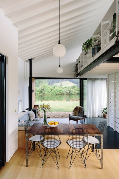 """A regional township south of Auckland was the ideal spot for architect Daniel Smith to build a modest """"kiwi bach"""" for his family overlooking the river and mountains. The exterior stands out for its cedar rain screen and the sloped and angled roof that makes the most of the home's small footprint. Paving the way to the sunken lounge is the showpiece kitchen, embracing affordable materials like pine, plasterboard, and black-painted aluminum."""