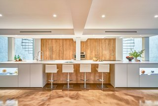 """We knew that if we wanted to increase the ceiling height, we needed to keep these column locations,"" architect Joanna Hartman says. ""So we let them set our island length."" The island is made from polished silestone."