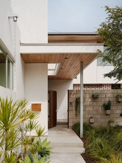 Stucco on the exterior keeps costs low and acts as a neutral backdrop for wood accents and drought-tolerant plants. The courtyard gate leads to the front door, which is out of street view.
