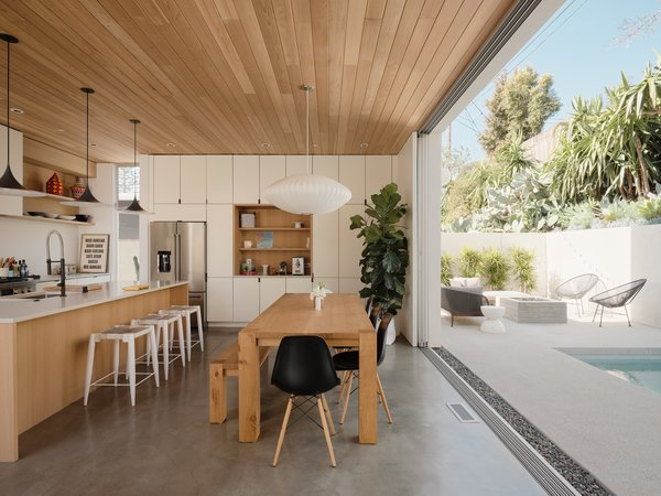 The L-shaped lot—and the decision to create a private courtyard and patio—made the kitchen and dining space the natural hub of the ground floor. Sweet installed full-length cabinetry on the western wall for storage, and included a wood niche for convenience.