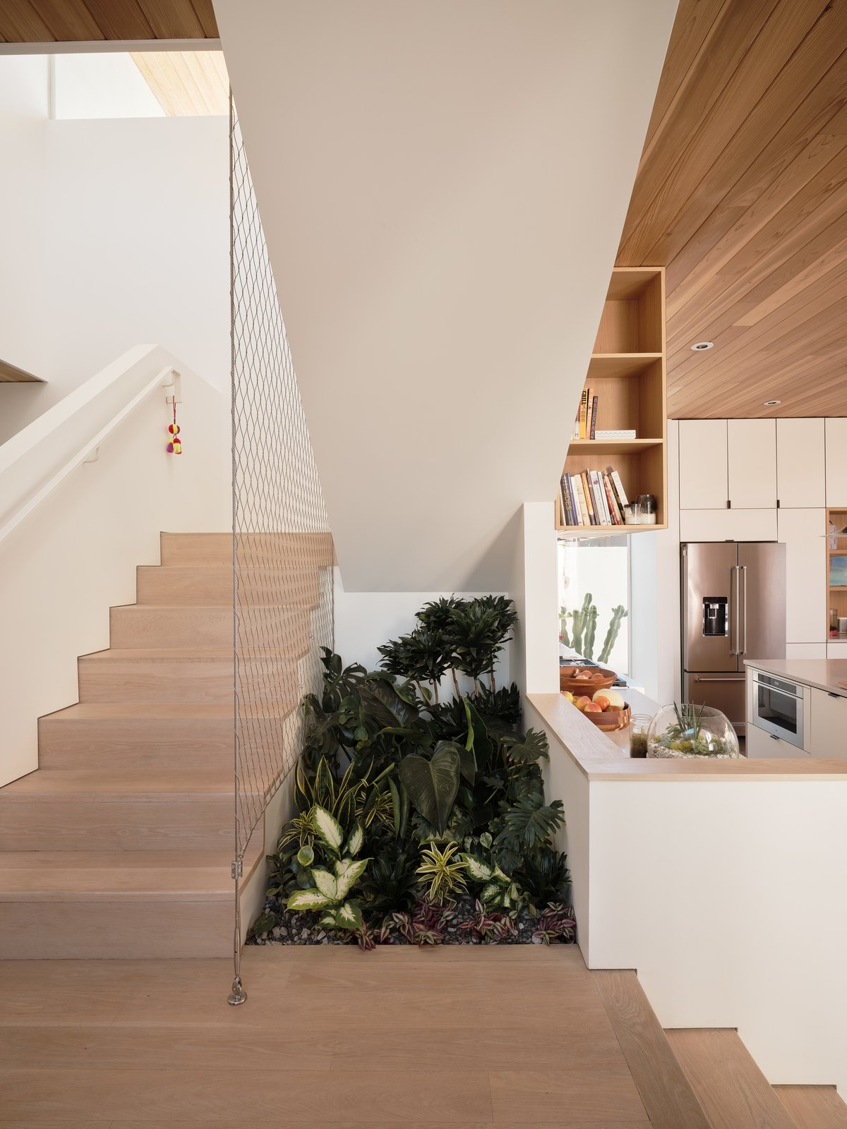 Courtyard House by Ras-a Studio wood staircase with mesh guardrail and live plants