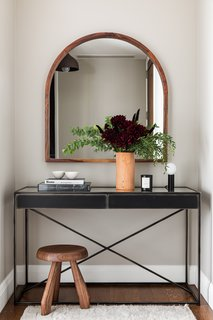 Restoration Hardware's Gramercy Console Table sits in the entryway above a custom mohair rug by Woven. The leather vase is by Jenni Kayne.