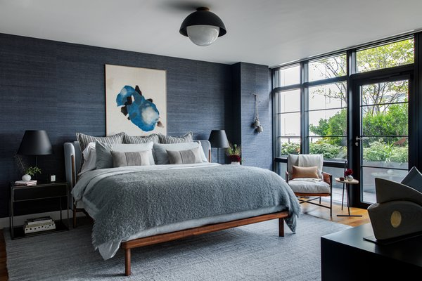 """A custom-made Nichetto bed by De La Espada sits beside a leather chair by Amber Lewis in the master bedroom. A """"Juicy Jute Grasscloth"""" wall covering by Phillip Jeffries adds more dimension to the blue room, which Becky enjoyed making slightly darker from the other spaces."""