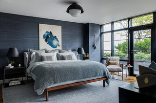 "A custom-made Nichetto bed by De La Espada sits beside a leather chair by Amber Lewis in the master bedroom. A ""Juicy Jute Grasscloth"" wall covering by Phillip Jeffries adds more dimension to the blue room, which Becky enjoyed making slightly darker from the other spaces."