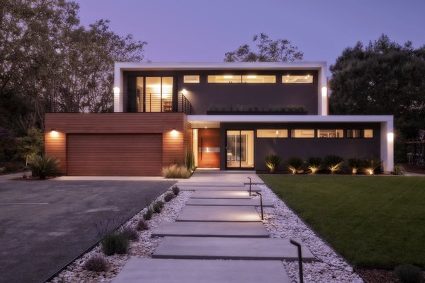 A concrete walkway leads to their home, which is painted in a custom white and gray stucco. The lighting is by Modern Form.