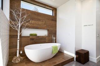 An Ethos bathtub contrasts woodwork by Porcelanosa in the master bathroom.