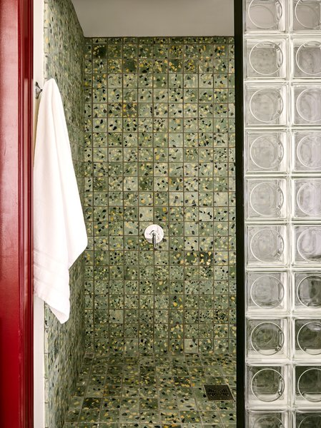 """""""By keeping the main color block in the showers, we tried to contain the chaos to a small and palatable space within the bathroom,"""" Cooper says. """"It's fun when you're in there, but you're not overwhelmed when using the bathroom for other purposes."""""""