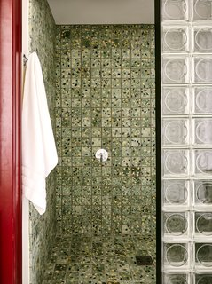 """By keeping the main color block in the showers, we tried to contain the chaos to a small and palatable space within the bathroom,"" Cooper says. ""It's fun when you're in there, but you're not overwhelmed when using the bathroom for other purposes."""