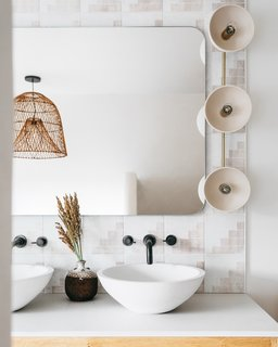 """The sink hardware is by Cal Faucets, and the sconces are by Triple Seven. """"We selected materials with subdued tones that still maintained visual interest,"""" Maziarski says."""