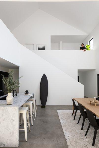 Laney LA选择了纯白色的石英岩作为厨房的台面,其纹理与地板上的裂缝相匹配。亚历克斯和艾丽卡接受了混凝土地板的不完美,他们喜欢它与白墙的对比。