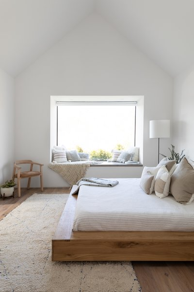A Casper mattress sits opposite a Klein Agency oak chair in the master suite. A West Elm lamp illuminates the reading nook at night.
