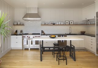 The kitchen countertops are made of oiled soapstone, and the backsplash features Heath Ceramics tiles. The island is a Carrara marble slab fitted onto an industrial base from Big Daddy's Antiques.