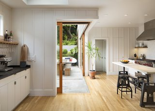 Fir-framed sliding glass doors match floating shelves made from the same wood. To create the open corner, Davis's team buried a steel beam in the ceiling.