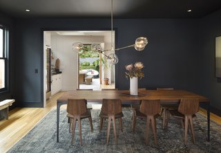 A custom-made black walnut dining table is surrounded by chairs from Matthew Hilton Designs. A Lindsey Adelman chandelier hangs overhead. The team chose to paint the dining room in Railings by Farrow and Ball to create a mood apart from the airier kitchen and living area.
