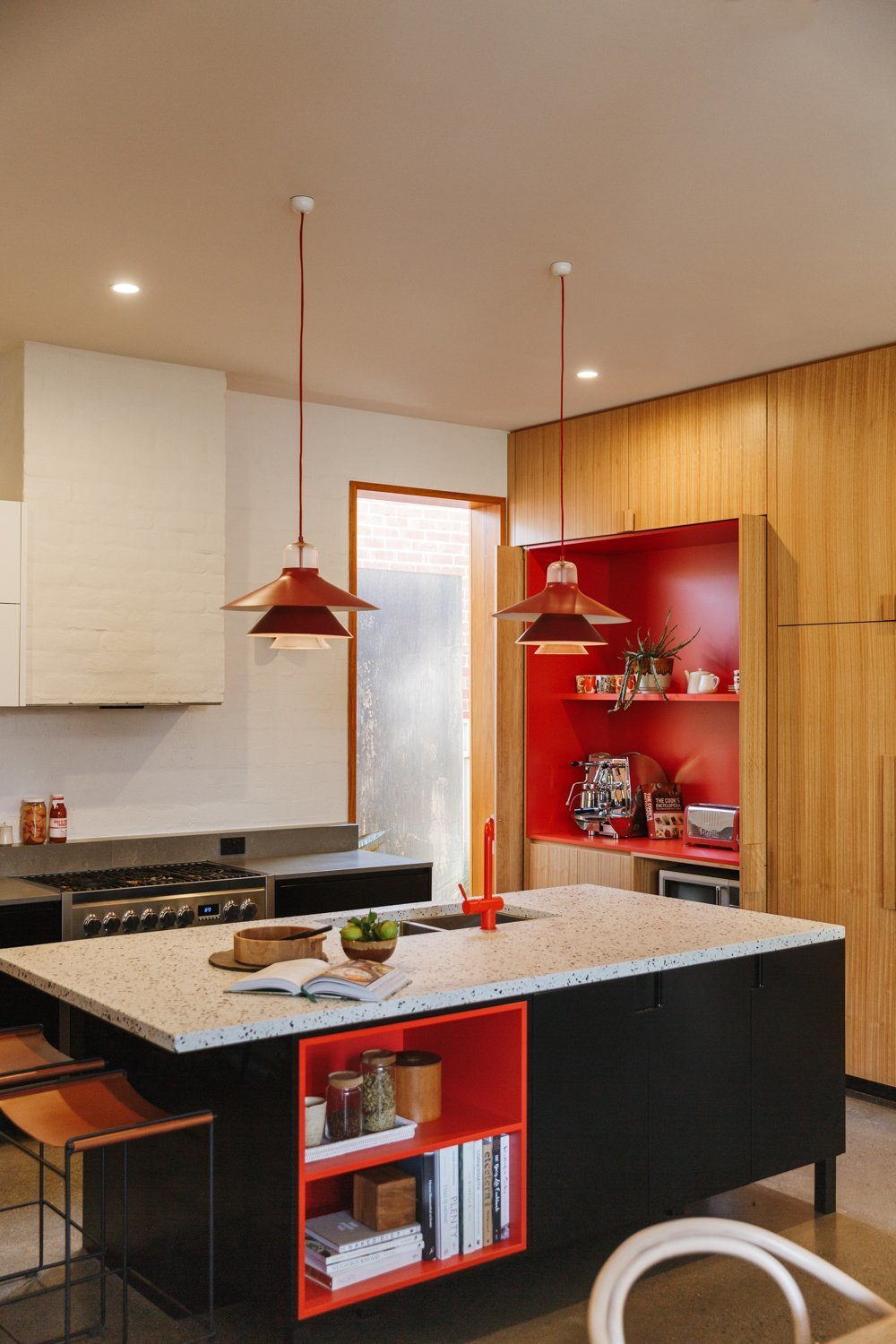 """Kitchen, Concrete Counter, Range, Pendant Lighting, Brick Backsplashe, Ceiling Lighting, and Wood Cabinet The owners asked for """"random pops of red"""" to flash throughout their kitchen renovation, complete with blackbutt wood, concrete countertops, and a terrazzo island.  Photo 3 of 9 in 9 Countertop and Cabinetry Pairings to Take Your Kitchen From Drab to Delicious"""