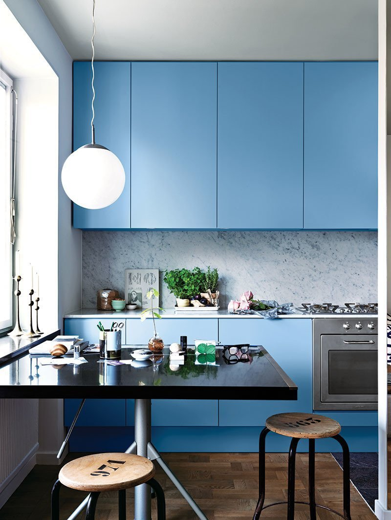 Kitchen, Colorful Cabinet, Dark Hardwood Floor, Range, Pendant Lighting, and Marble Backsplashe A compact stove and oven are hidden within the blue cabinetry.   Photo 7 of 9 in 9 Countertop and Cabinetry Pairings to Take Your Kitchen From Drab to Delicious