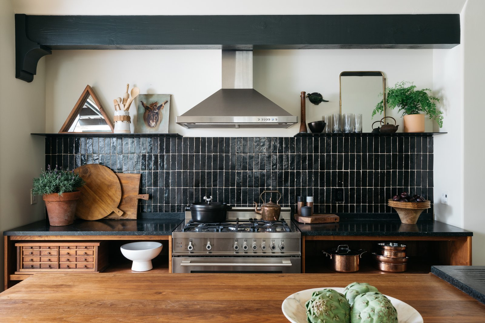 Kitchen, Wood Cabinet, Range, Subway Tile Backsplashe, and Stone Counter Emily Henderson styled this kitchen, using greenery and mirrors to lighten its moody aesthetic.  Photo 8 of 9 in 9 Countertop and Cabinetry Pairings to Take Your Kitchen From Drab to Delicious