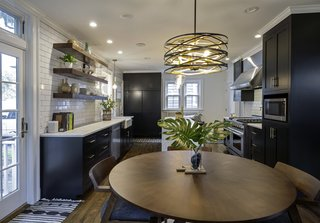 A Minka-Lavery pendant light hangs above the dining area off the patio. On the far end of the kitchen is the broom closet.