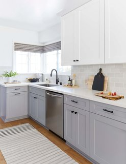 "Macdonald opted for a traditional Shaker cabinet for the kitchen and laundry room, but painted the uppers in Benjamin Moore's ""Chantilly Lace"