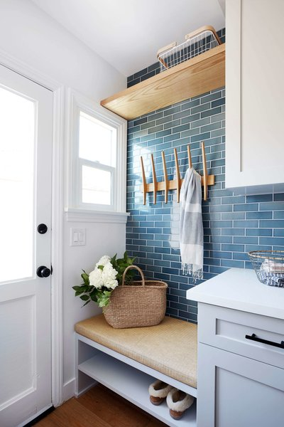 """Rejuvenation wall hooks match the shade of the bench cushion. The laundry room's Heath tiles are colored in """"Heron Blue."""""""