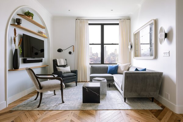 """""""Curves felt like a small but significant detail in making the space feel more generous,"""" Robinson says. The media niche is accented with custom white oak shelving with rounded corners and a flat-edge profile. Opposite sits a sectional and recliner from Room & Board. The handmade rug is from Kravet, the side tables are from Design Within Reach, and the vintage mirror is from Baker Furniture."""
