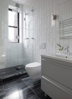 A Duravit vanity and Grohe faucet in the bathroom are paired with Catia Black marble tile on the floors, and floor-to-ceiling ceramic subway tile on the walls.