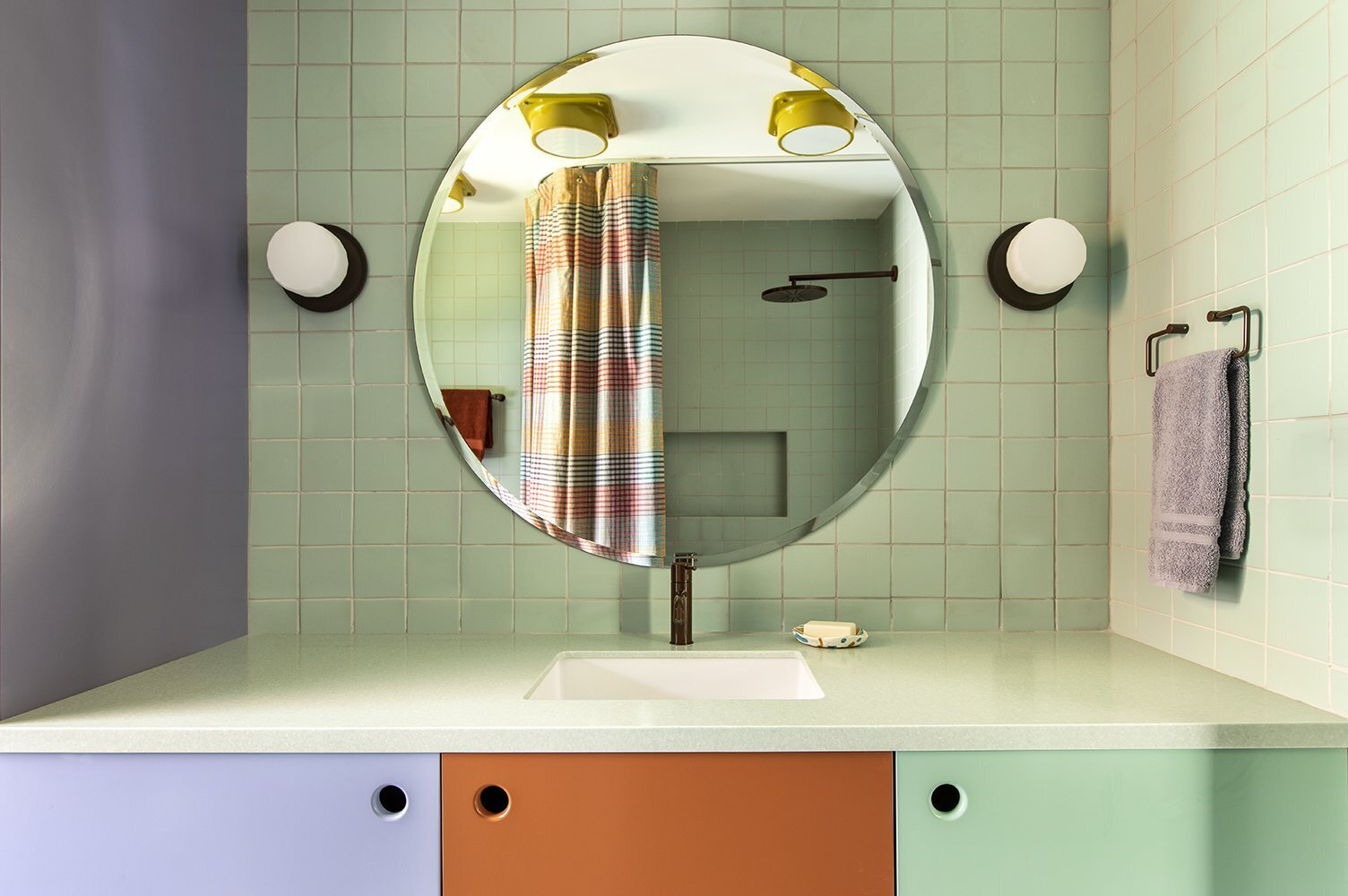 bathroom with green tile and colorful cabinets