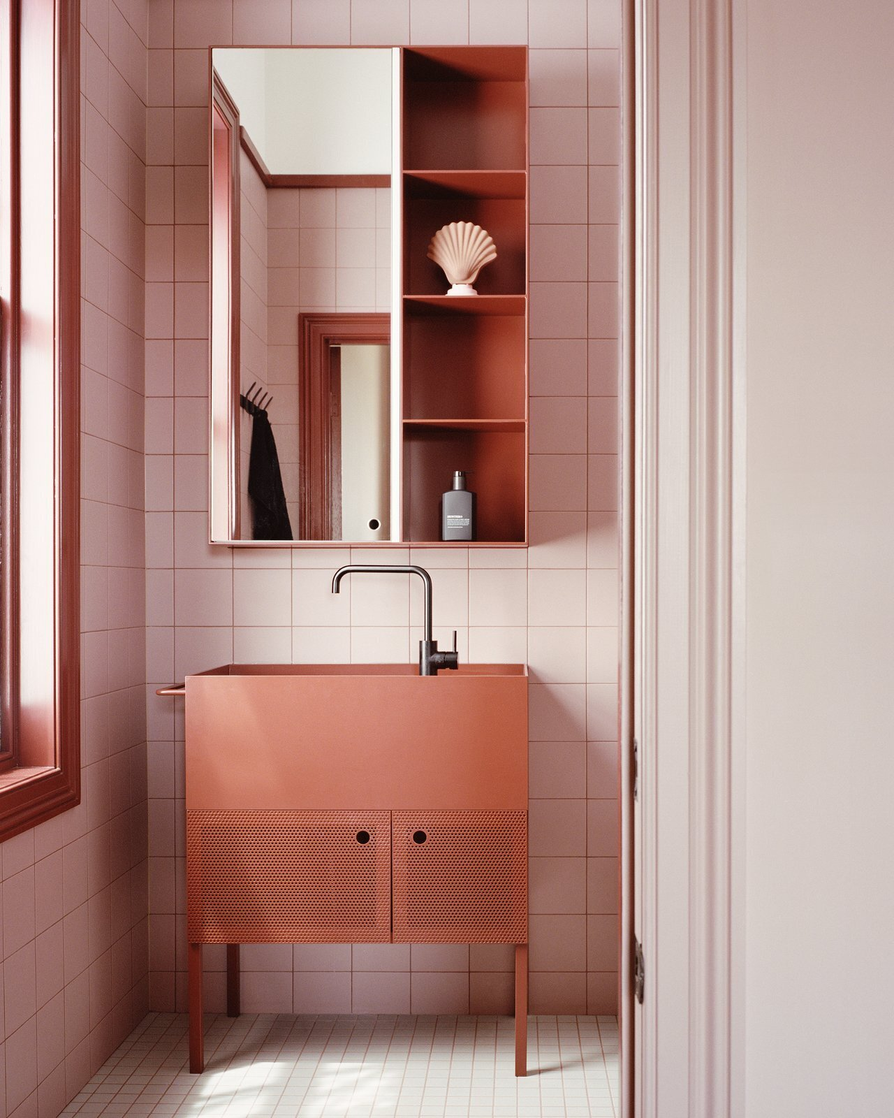 bathroom with pink tile and red washbasin