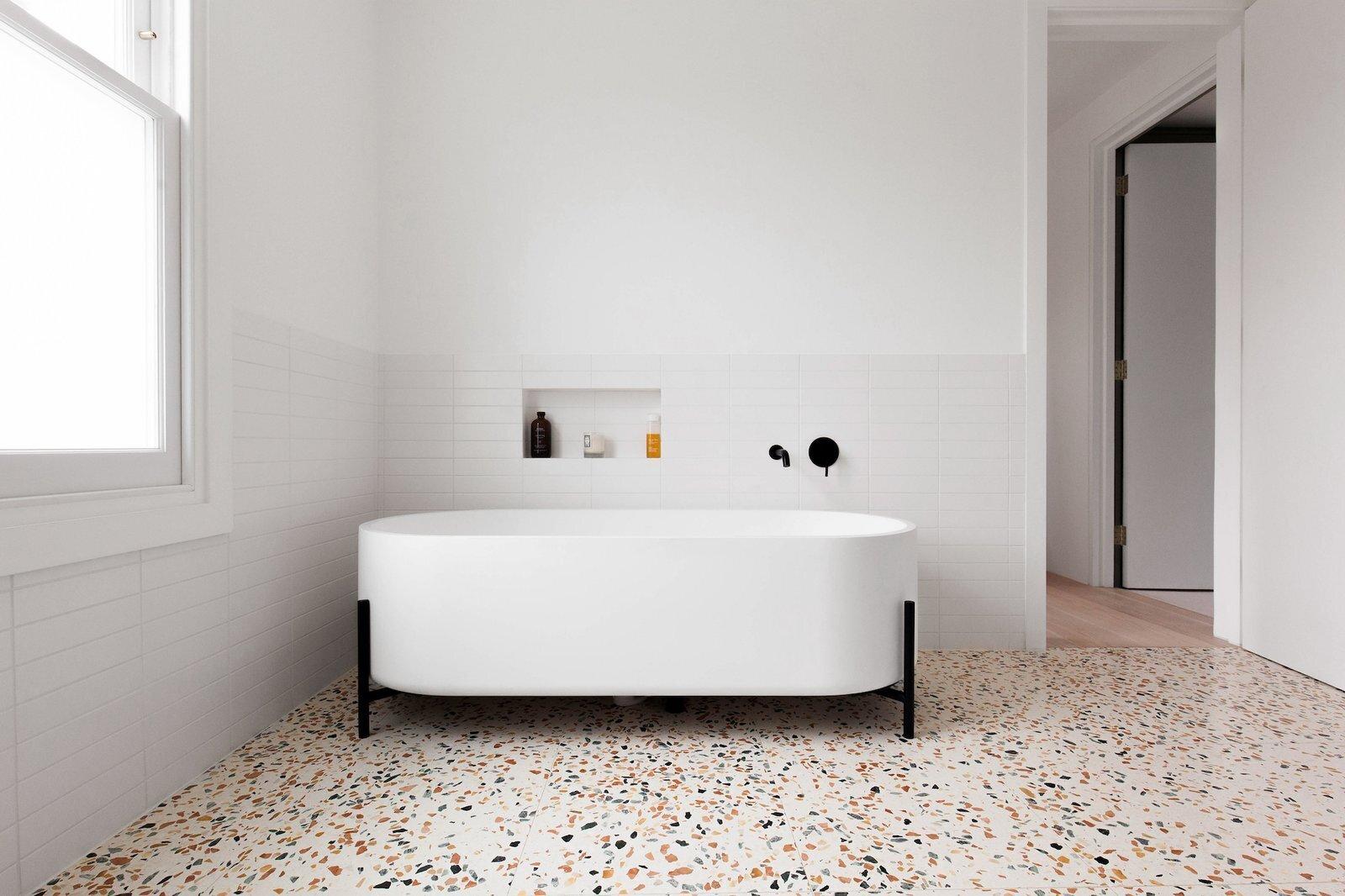bathroom with terrazzo floors and white tile