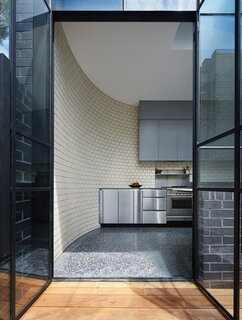 La Paloma Miro brick meets charcoal-colored polished concrete in the kitchen. A stainless-steel backsplash matches the bottom set of cabinetry.