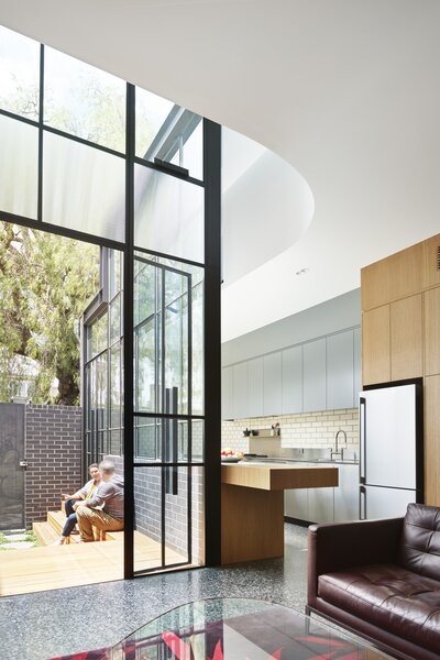 """The galley-style kitchen on the south boundary has a slim footprint compared to the rest of the house, and allows for north-facing windows almost measuring 16 feet in height,"" says Naughtin. ""The windows can be opened to draw warm air up and out of the space."""