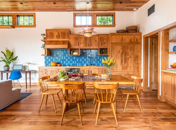 Custom cabinetry, countertops, and a dining table were crafted from salvaged wood.