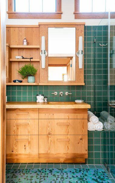Green tiles complement an oversized vanity in the bathroom, which gets lot of natural light.