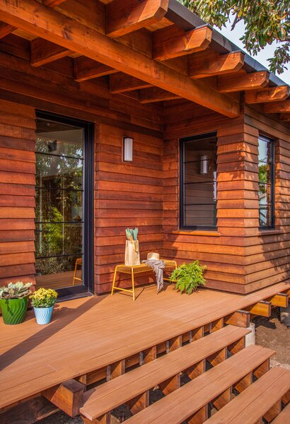 Reclaimed wood graces the exterior and wraparound deck of the ADU, which is surrounded by native landscaping.