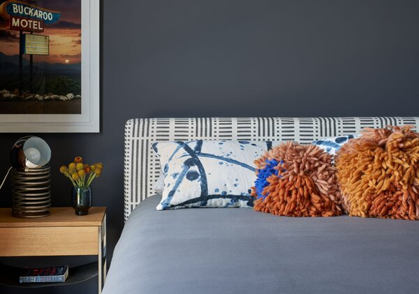 Bold patterns mix in one of the bedrooms, which also has its share of art.