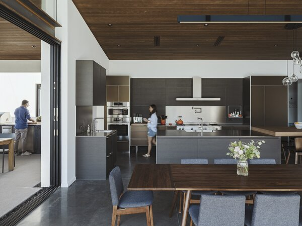 Bronze, aluminum, and black oak were used as part of the kitchen design. A stainless monobloc island is surrounded by polished quartz countertops on the perimeter.