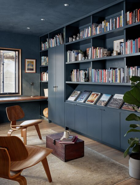 A new office sits at the front of the house, and its moody walls and bookshelves contrast the other rooms' mostly light and neutral palette.