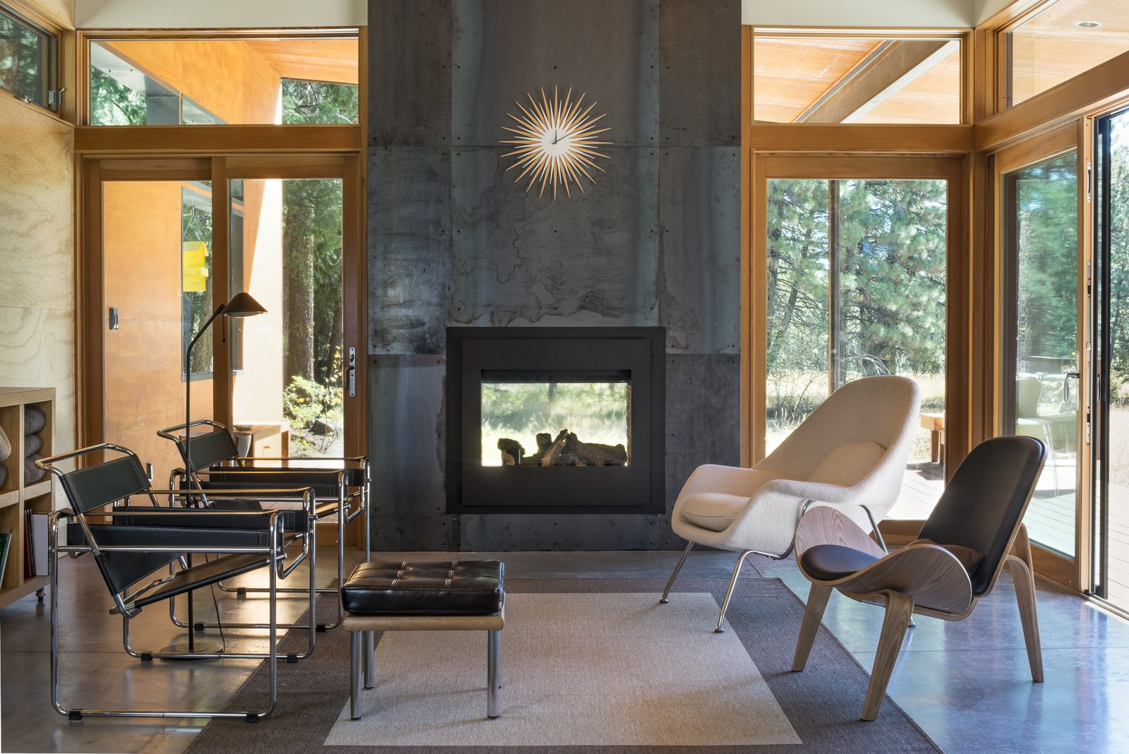 Living Room, Concrete Floor, Floor Lighting, Rug Floor, Chair, Two-Sided Fireplace, and Ottomans The interior living room, on the reverse of the double-sided fireplace.  Lot 6 by Prentiss + Balance + Wickline Architects