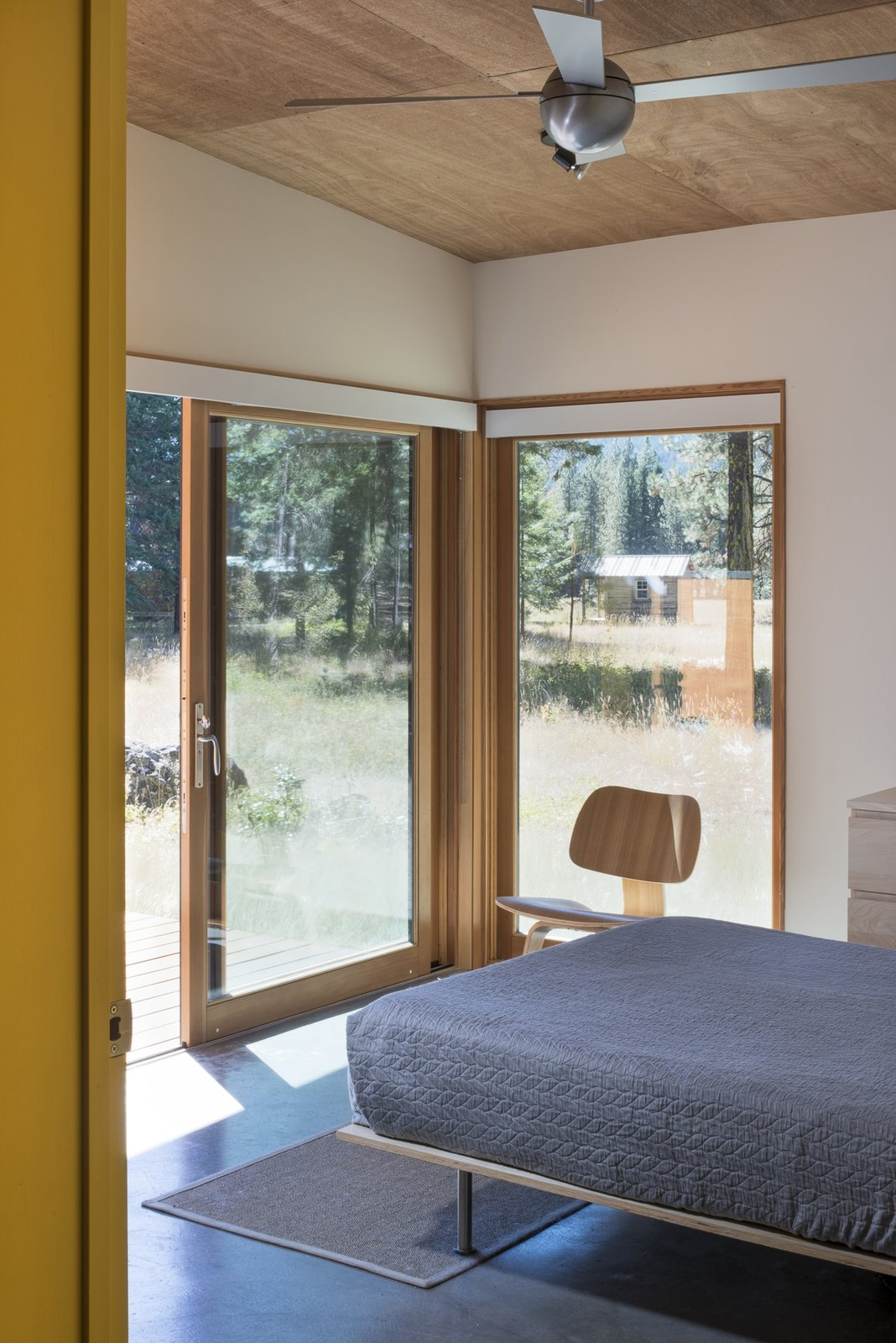 Bedroom, Chair, Rug Floor, Bed, and Concrete Floor The bedroom opens out onto the deck and meadow beyond.  Lot 6 by Prentiss + Balance + Wickline Architects