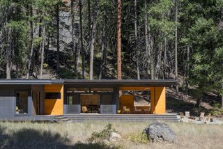 Nestled at the base of a dramatic rocky butte, a tiny cabin in the woods of Washington blurs the distinction between indoors and out.