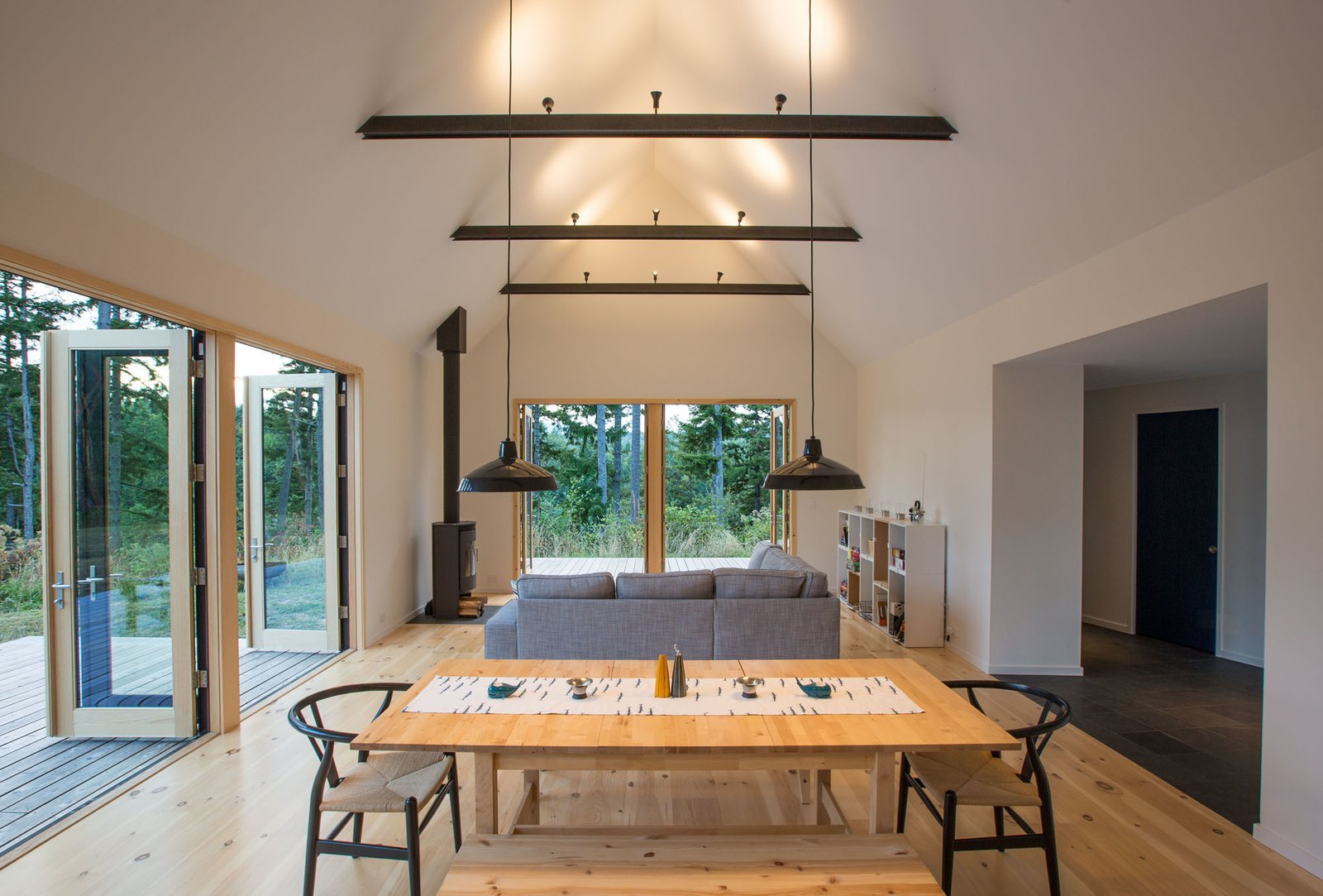 "Dining Room, Chair, Table, Track Lighting, Pendant Lighting, and Light Hardwood Floor The ""great room"" extends out to decks on two sides, creating a cozy yet expansive space for comfortable, easy living.  The Coyle by Prentiss + Balance + Wickline Architects"