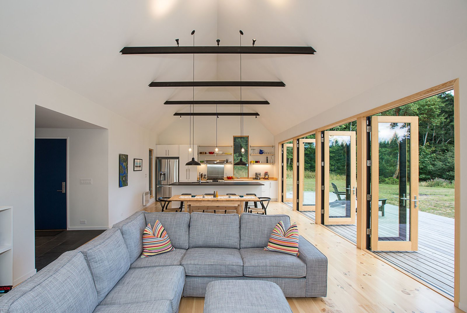 Living Room, Sofa, Pendant Lighting, Track Lighting, and Light Hardwood Floor A combination of carefully chosen furniture and finishes, including pine flooring and trim, warms up the lofty white interior.  The Coyle by Prentiss + Balance + Wickline Architects