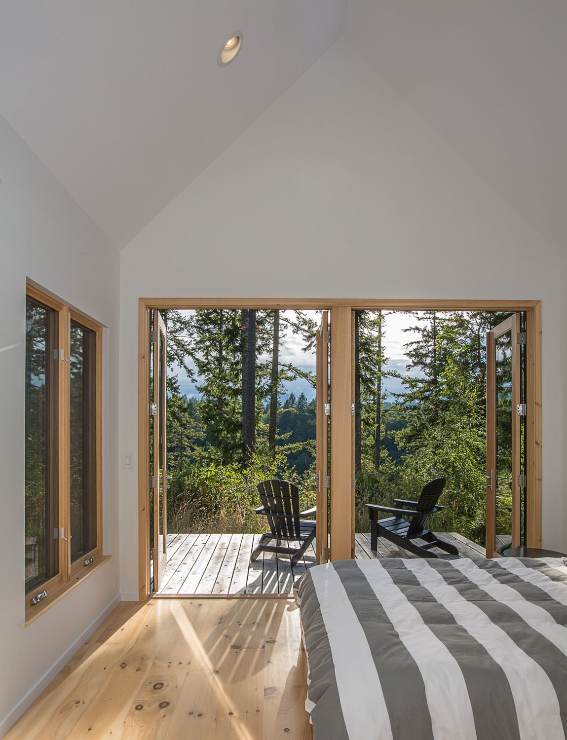 Bedroom, Bed, Light Hardwood Floor, and Recessed Lighting In the master bedroom, Douglas firs filter the light and mountain views for a more intimate experience.  The Coyle by Prentiss + Balance + Wickline Architects