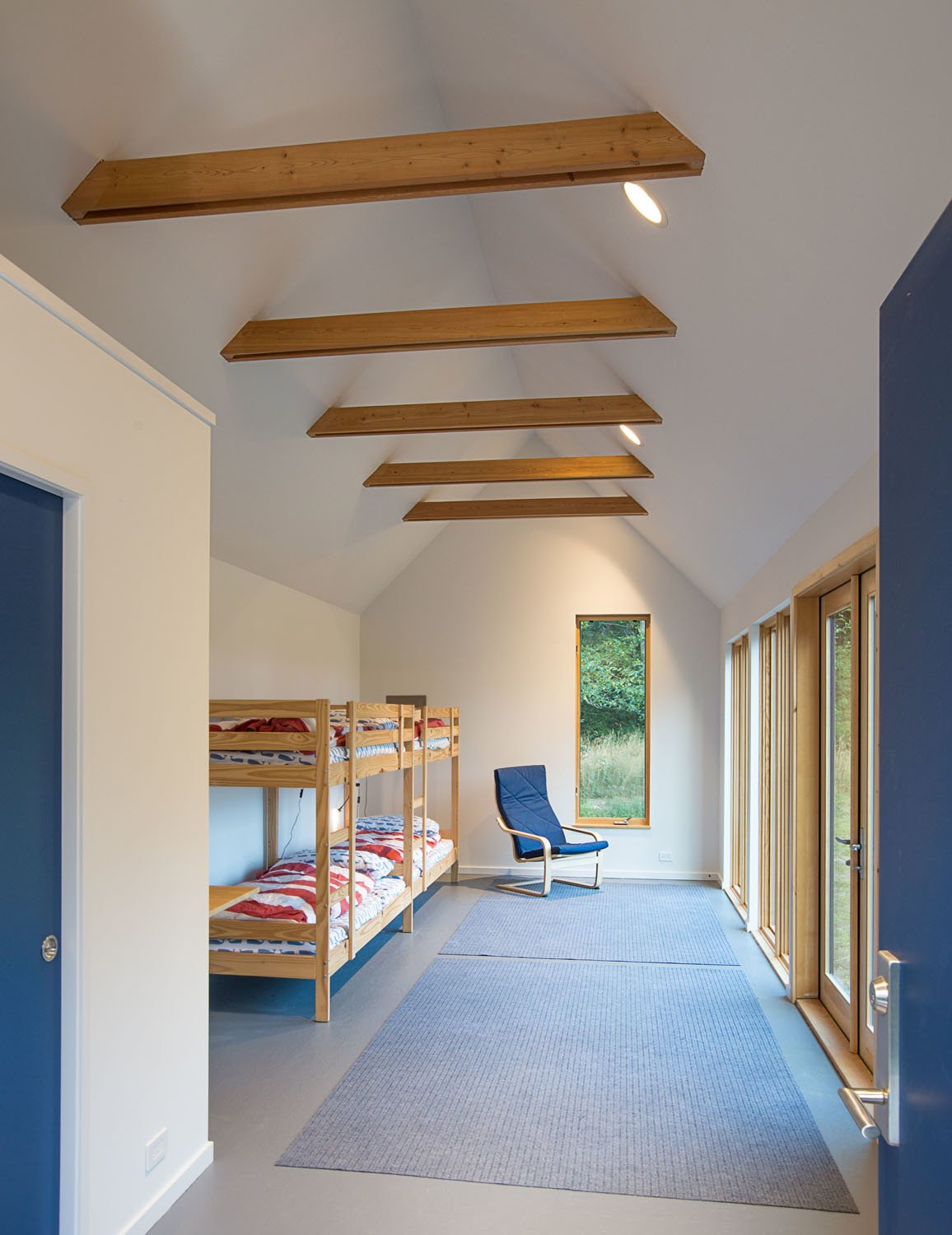 Kids Room, Bedroom Room Type, Toddler Age, Bunks, Pre-Teen Age, Neutral Gender, Chair, and Rug Floor An existing structure was moved, remodeled, and repurposed as a bunkroom.  Photos from The Coyle