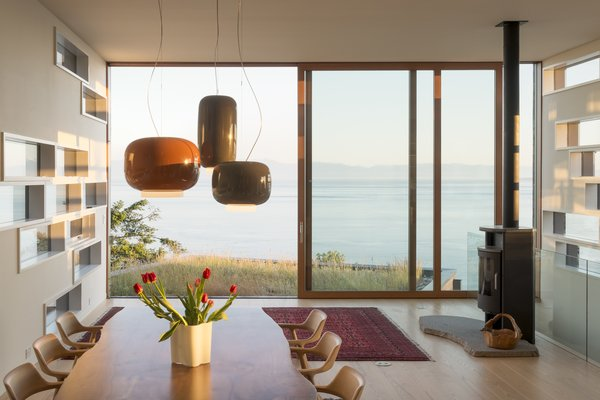 Oversized sliding glass doors at the end of each volume form window walls directed at specific views, while clusters of smaller horizontal lites let in natural light and glimpses of the surrounding landscape.