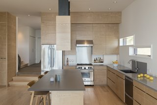 A small stepping transition from the entryway marks the boundary of the kitchen, which flows seamlessly into the dining and living areas for an airy, comfortable space.