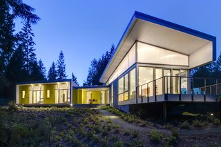 The main house includes a generous amount of outdoor space, extending the living area into the surrounding forest.