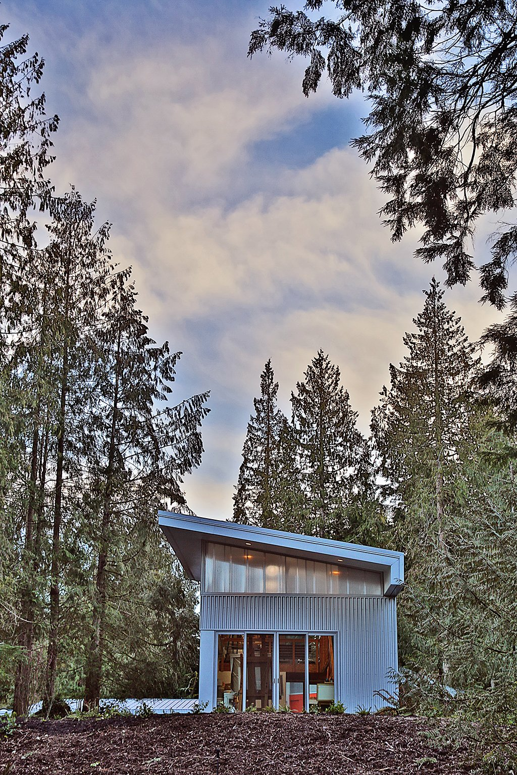 Exterior, House Building Type, and Cabin Building Type The exterior aesthetic confidently contrasts to its natural setting, creating discrete objects carefully set into the landscape.  Whidbey Artists' Retreat by Prentiss + Balance + Wickline Architects